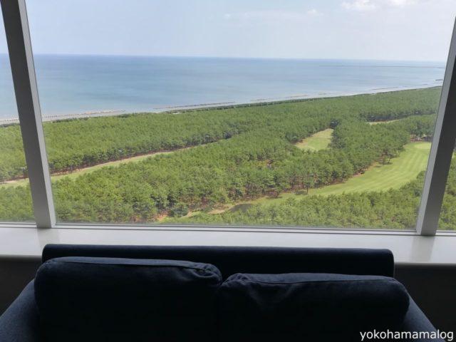 ソファーの後ろには青い空と海、緑の松林が広がっています。