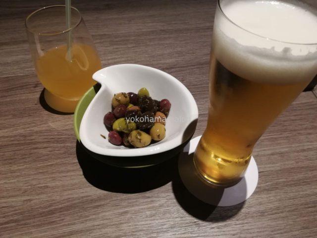 お風呂上りに「オリーブマリネ」とビールですよね。奥にあるのはリンゴジュースです。